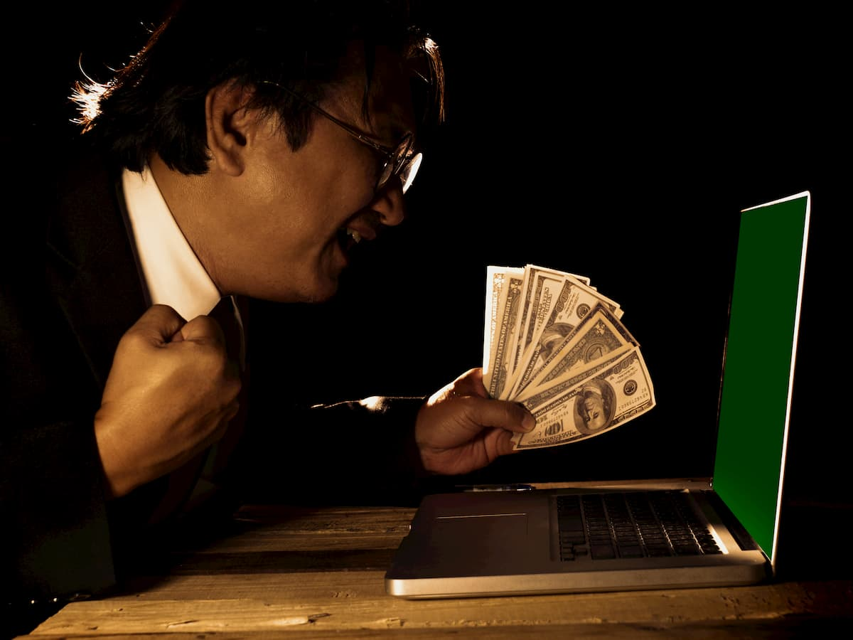 gambler in front of his laptop with money to gamble